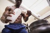Body builder scooping up protein powder — Stock Photo