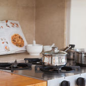 Stove top with saucepan and recipe book — Stock Photo