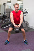 Strong man lifting heavy kettlebell — Stockfoto