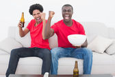 Football fans in red sitting on couch with beer and popcorn — Stock Photo