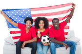 Happy football fans in red sitting on couch with usa flag — Stock Photo