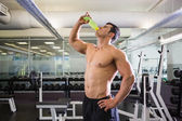 Shirtless muscular man drinking energy drink in gym — Stock Photo