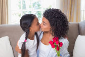 Pretty mother kissing her daughter holding roses — Stock Photo