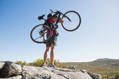 Fit man carrying his bike on rocky terrain — Stock Photo
