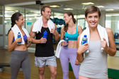 Fit woman smiling at camera in busy fitness studio — Stock Photo