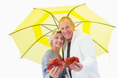 Happy mature couple showing autumn leaves under umbrella — Stock Photo