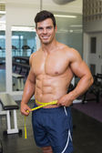 Shirtless muscular man measuring waist in gym — Stock Photo
