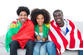 Happy football fans wrapped in flags smiling at camera — ストック写真