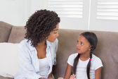 Pretty mother sitting on the couch scolding her daughter — Stock Photo
