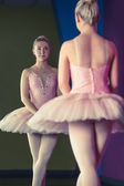 Graceful ballerina standing in first position in front of mirror — Stock Photo