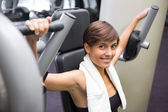 Happy brunette using weights machine for arms — Foto Stock