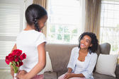 Daughter hiding bouquet of roses for mother — Stock Photo