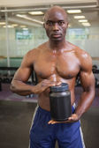 Muscular man with nutritional supplement — Stock Photo