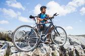 Cyclist taking break on rocky peak — Stock Photo
