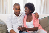 Cute couple relaxing on couch with smartphone — Stockfoto