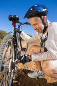 Smiing cyclist fixing his bike chain on country terrain — Stock Photo