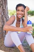A mulher apta sentado contra árvore segurando garrafa de água — Foto Stock