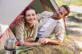 Outdoorsy couple smiling at camera inside their tent — Stock fotografie