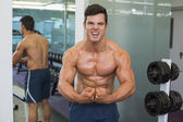 Shirtless muscular man flexing muscles in gym — Foto de Stock