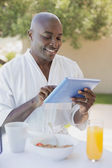 Handsome man in bathrobe using tablet at breakfast outside — Stock Photo