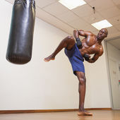 Muscular boxer kicking punching bag in gym — Stock Photo