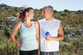 Active couple embracing each other on a jog in the country — Stock Photo