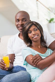 Happy couple sitting on couch having juice — Stock Photo