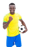 Football player in yellow celebrating a win — Stock Photo