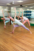 Yoga class in extended triangle pose in fitness studio — Stock Photo