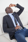 Tired businessman getting headache on the sofa — Stock Photo