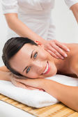 Beautiful brunette enjoying a shoulder massage — Stock Photo