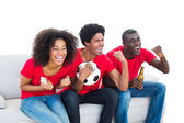 Cheering football fans in red sitting on couch — Stok fotoğraf