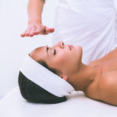 Peaceful brunette getting reiki therapy — Stock Photo