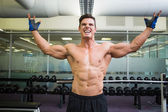 Shirtless bodybuilder with arms raised in gym — Stock Photo