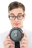 Geeky businessman holding alarm clock — Foto Stock