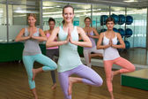 Smiling yoga class in tree pose in fitness studio — Stock Photo