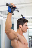 Shirtless male body builder doing pull ups at the gym — Stock Photo