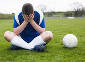 Disappointed football player in blue — Stockfoto