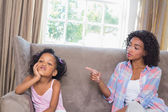 Pretty mother scolding her daughter on the couch — Stock Photo