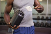 Body builder holding a scoop of protein mix in gym — Stock Photo