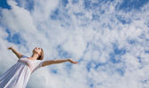 Woman with arms outstretched against blue sky and clouds — Stockfoto