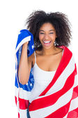 Pretty girl wrapped in american flag smiling at camera — Foto de Stock