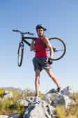 Fit cyclist carrying his bike on rocky terrain — Stock Photo