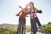 Fit cyclist couple looking around on mountain trail — Stock Photo