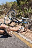 Cyclist lying on the road after an accident — 图库照片
