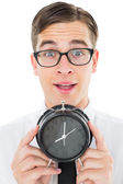 Geeky businessman holding alarm clock — Φωτογραφία Αρχείου