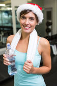 Fit brunette in santa hat smiling at camera — Стоковое фото