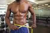 Muscular man measuring waist in gym — Stock Photo