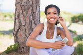 Fit woman sitting against tree listening to music — Stockfoto