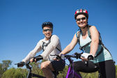 Active happy couple going for a bike ride in the countryside — Stock Photo